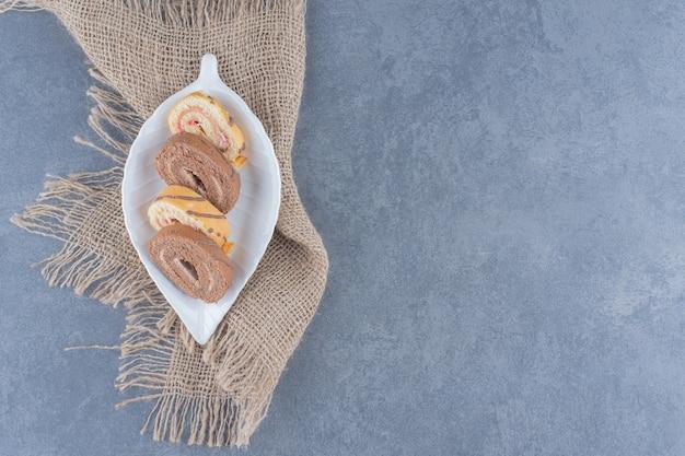 Torta arrotolata affettata nel piatto sull'asciugamano sul tavolo di marmo