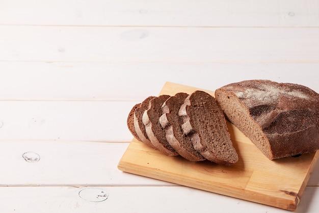 Pane di segale affettato sul tagliere sulla tavola di legno bianca