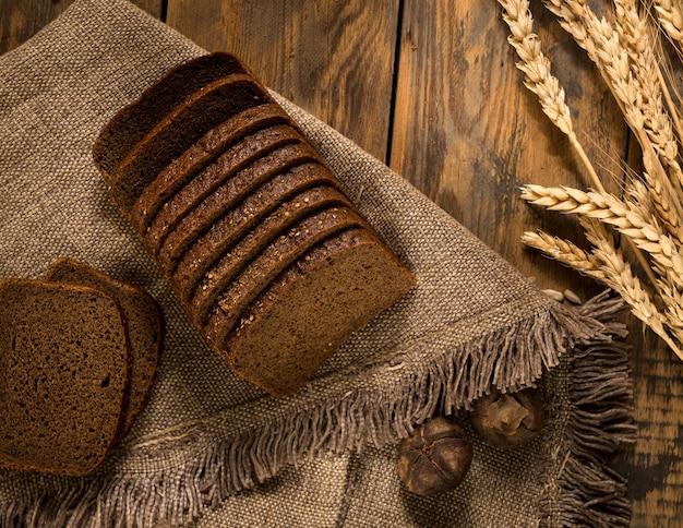 Pane di segale affettato su un tovagliolo e spighette su una superficie di legno, vista dall'alto