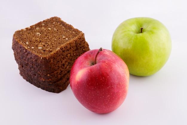 Pane di segale affettato su una superficie bianca con mele verdi e rosse