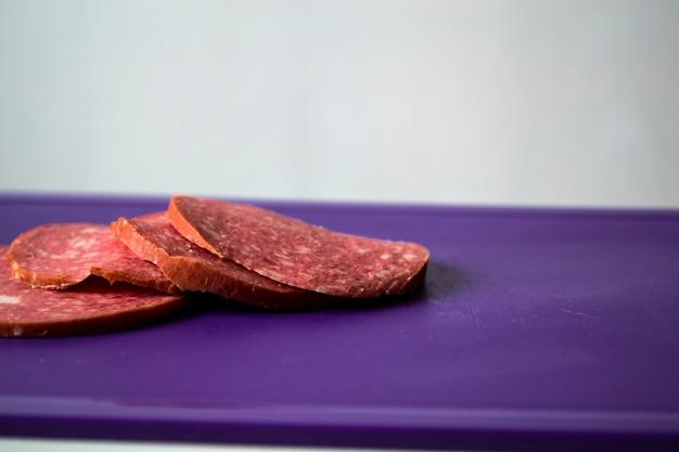 Fette rotonde di salsiccia affettata e una pagnotta di salsiccia su un tono bianco