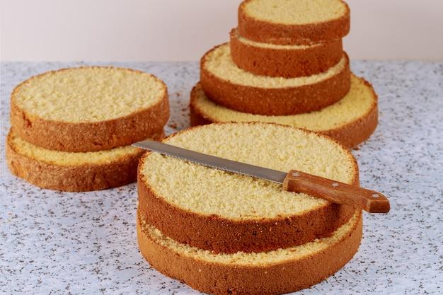 Pan di spagna affettato con il coltello sulla tavola per produrre la torta nunziale