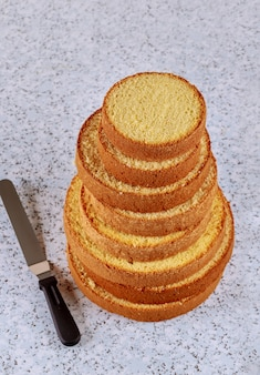 Pan di spagna affettato con la spatola sulla tavola per produrre la torta nunziale