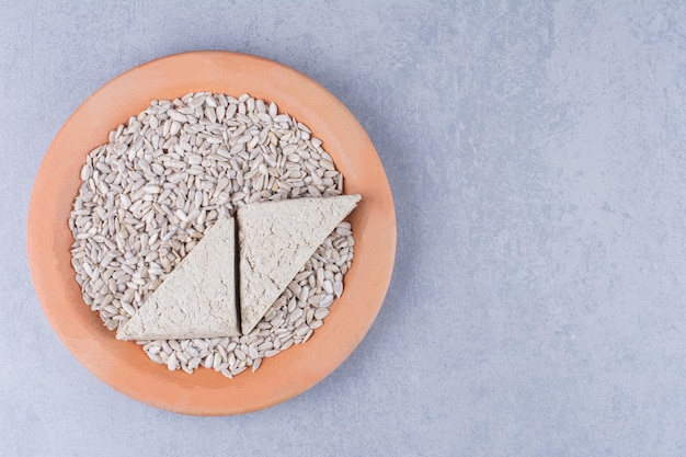 Halva di girasole a fette e semi sbucciati su un piatto sulla superficie di marmo
