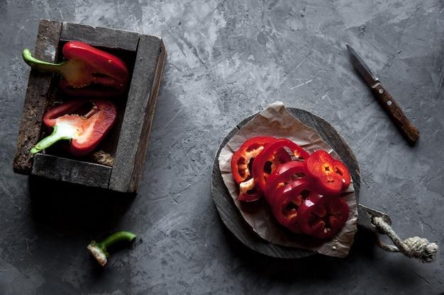 Peperone dolce a fette su un tagliere con un coltello e pepe maturo.