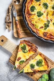 Crostata a fette con salmone, broccoli e panna su un tagliere di legno. vista dall'alto.