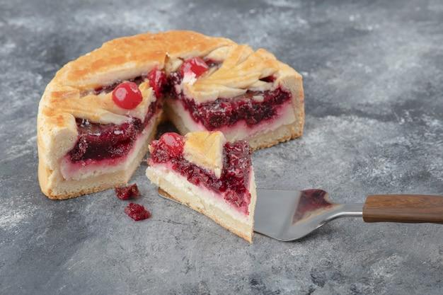 Affettato gustoso cheesecake con frutti di bosco posto sulla superficie di marmo.
