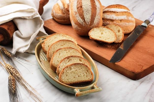 Fette di pane tostato pane bianco (shokupan o roti tawar) per colazione su fondo di legno, servito con uova e latte. immagine del concetto di panetteria