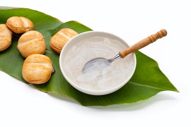 Toddy a fette di palma sciroppata in una ciotola bianca con cucchiaio su foglia verde