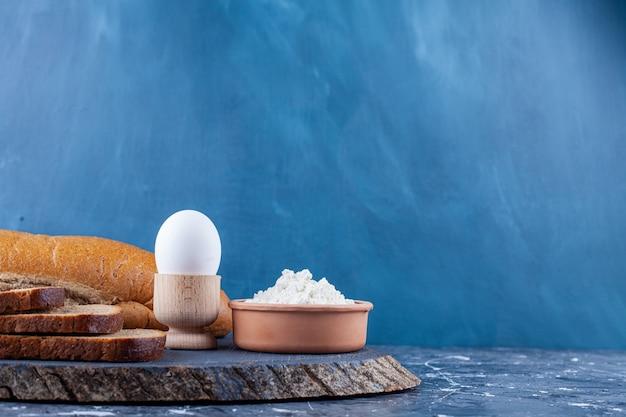 Fette di vari pane, uova e ciotola di farina sul pezzo di legno.