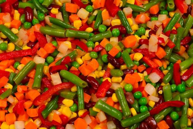 Verdure a fette, mais, fagioli, piselli, carote, sfondo di peperoni dolci.