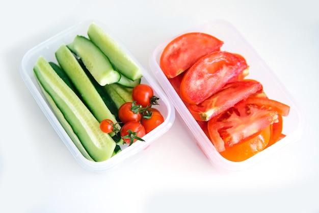 Verdure affettate in contenitori di plastica su sfondo bianco. cetrioli e pomodori sono in contenitori. alimentazione sana e corretta. pranzo al sacco per lavoro o viaggio.