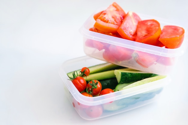 Verdure affettate in contenitori di plastica su sfondo bianco. cetrioli e pomodori sono in contenitori.
