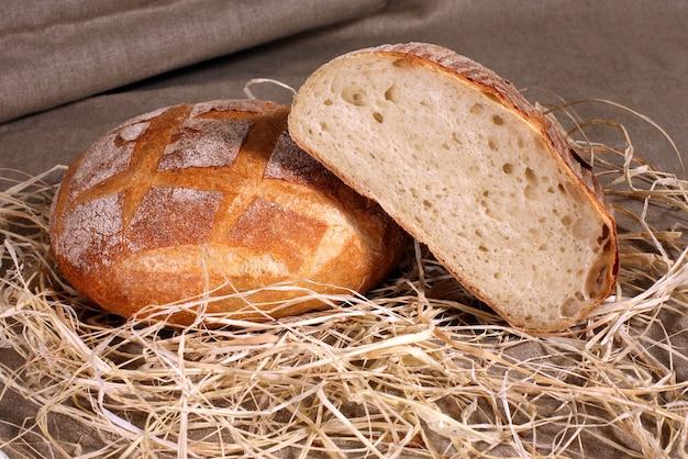 Fette di pane bianco che giace nella paglia sulla tovaglia di lino grigio
