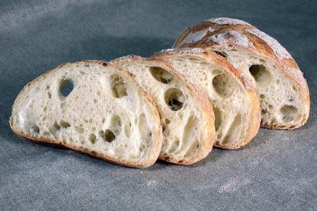 Fette di pane bianco adagiato sulla tovaglia in lino grigio