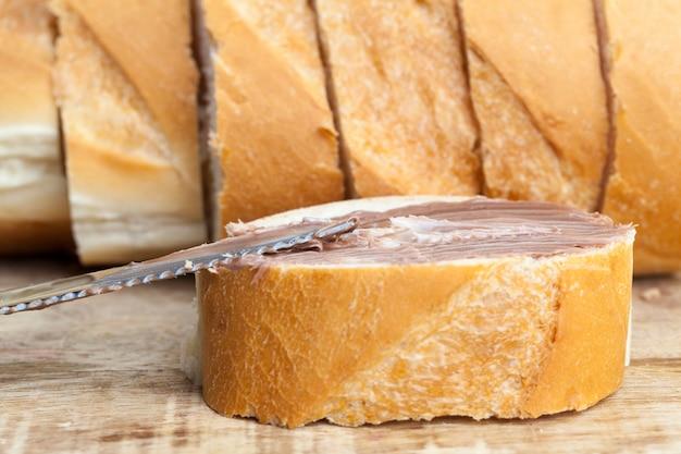 Pane bianco a fette con crema di burro dolce al cioccolato, burro morbido al cioccolato e pane bianco, pasta di cioccolato al cacao naturale durante la colazione, coltello in metallo