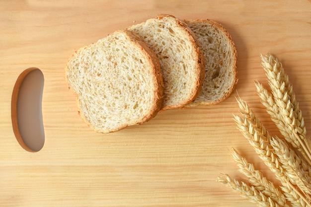 Fette di pane integrale e spighe di grano su tagliere di legno.
