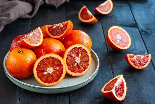 Fette e intere arance rosse siciliane mature su fondo di legno scuro