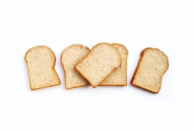 Pane integrale affettato su priorità bassa bianca.