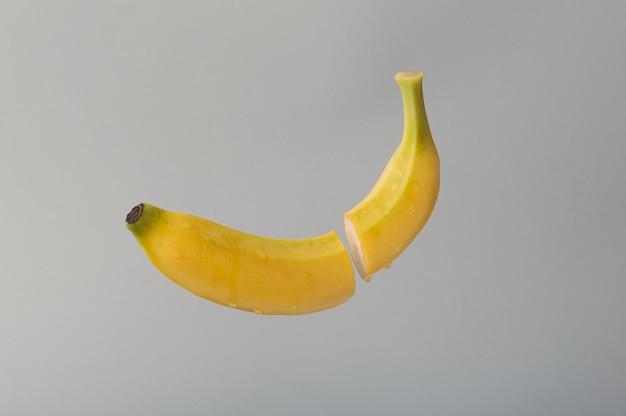 Una banana gialla affettata nell'aria con gocce d'acqua sfondo grigio concetto alimentare