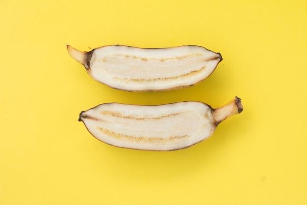 Banana gialla affettata su sfondo giallo