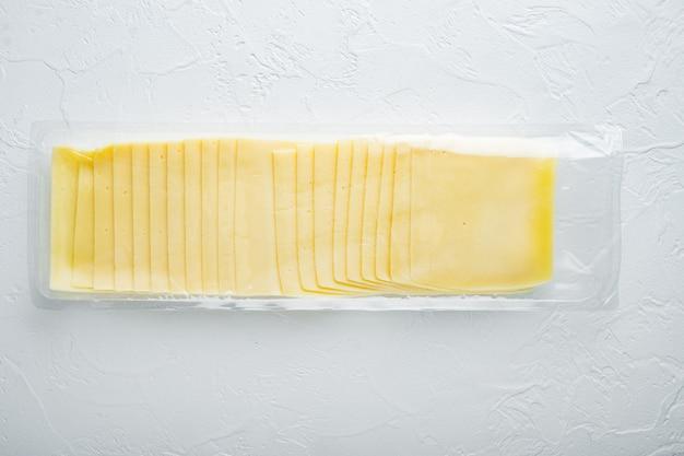 Fette di formaggio americano in confezione di plastica, sul tavolo bianco