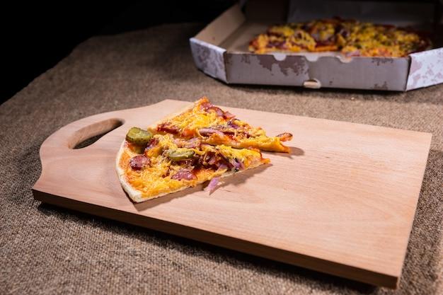 Fette di pizza artigianale su tagliere in legno con scatola di cartone da asporto sullo sfondo su tavolo ricoperto di tela
