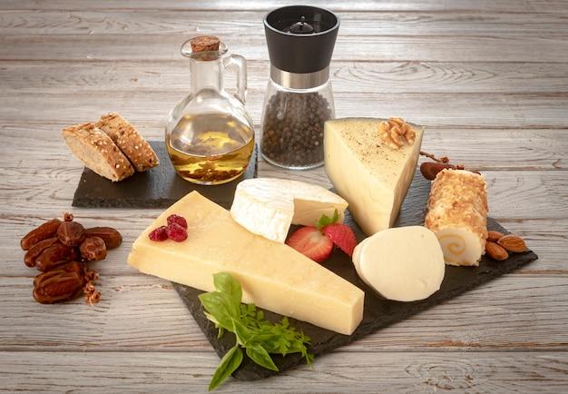 Fette di formaggio francese, spagnolo e italiano assortiti su una tavola scura, servite con pane e frutta secca, fondo di legno