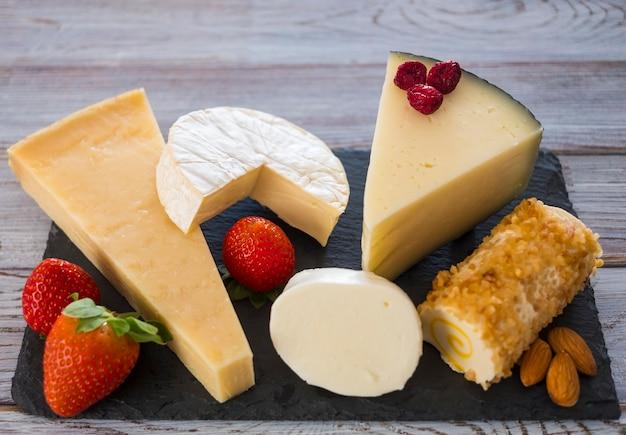 Fette di formaggio francese, spagnolo e italiano assortiti su una tavola scura, servite con frutta, fondo in legno