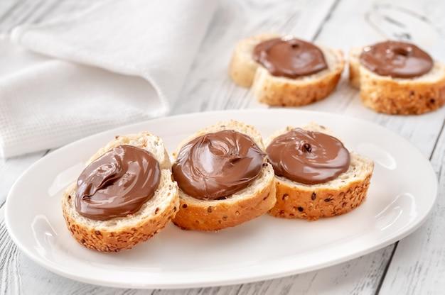 Fette di baguette con pasta di cioccolato sulla piastra bianca