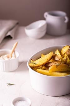 Fette di patate al forno con rosmarino e olio in una ciotola