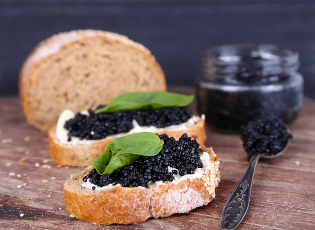 Fette di pane con burro e caviale nero su tavola di legno su sfondo scuro