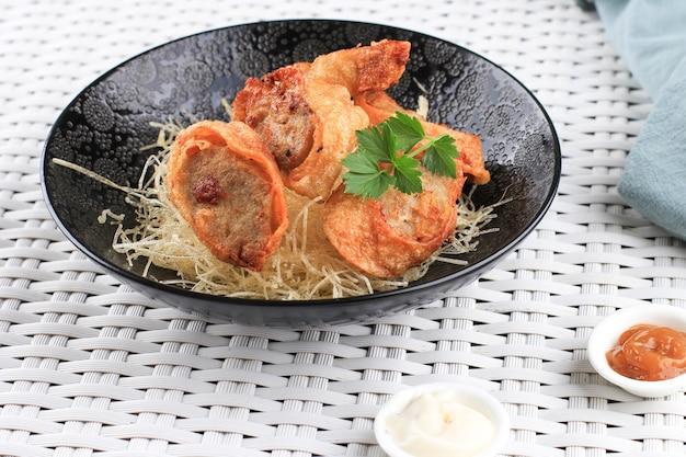 Fette di involtini di uova di pollo, sono uova di frittata ripiene di pollo macinato e spezie, al vapore e fritte, servite con salsa maionese al peperoncino sopra vermicelli croccanti