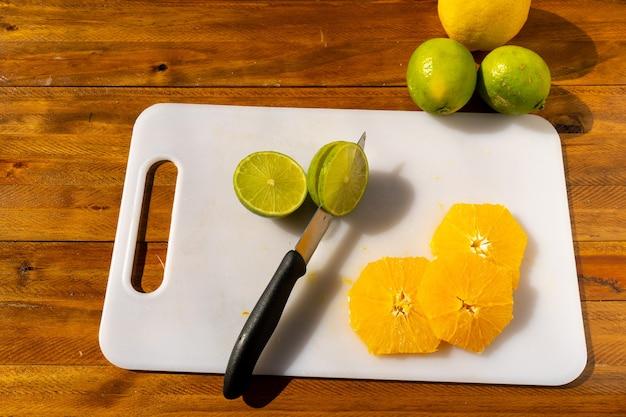 Fette di agrumi lime e arancia appena tagliate su un tagliere bianco con un coltello