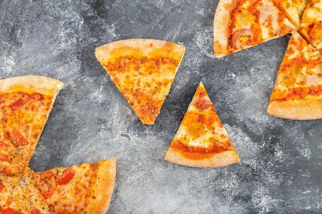 Fette di deliziosa pizza di formaggio posizionata su sfondo di pietra.