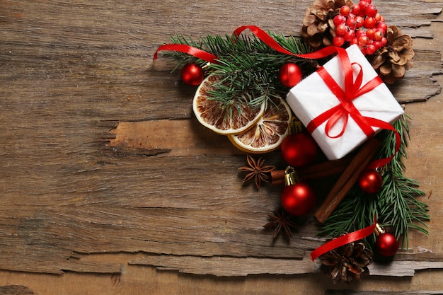 Fette di limone essiccato con scatola regalo, palline e rametto di albero di natale su fondo di legno rustico