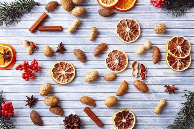 Fette di arancia essiccata e limone con noci e spezie su tavolo in legno colorato