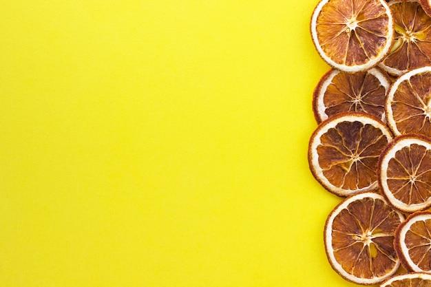Fette di arancia secca su giallo