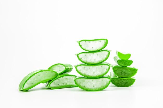 Fette di pianta fresca di aloe vera impilate e gambo o foglie di aloe vera con acqua che cade isolato su bianco