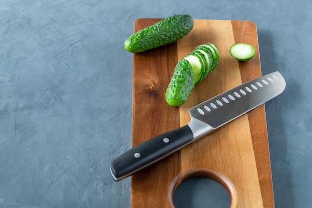 Fette di cetrioli freschi sul tagliere con un coltello da cucina sulla superficie scura