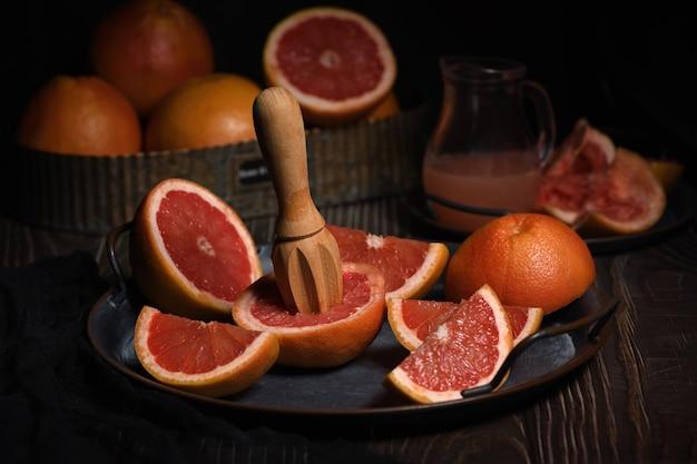 Fette di pompelmo fresco preparato per la produzione di spremute fresche su un piatto, sfondo scuro
