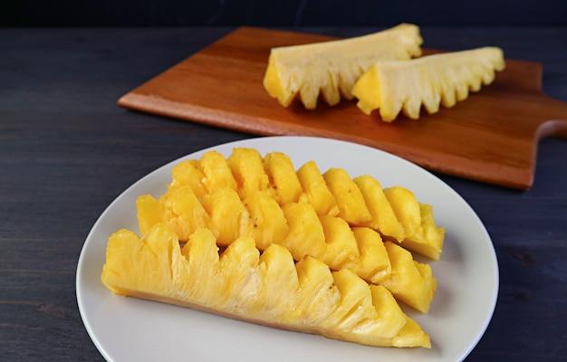 Fette di ananas maturo fresco in un piatto bianco pronto a servire