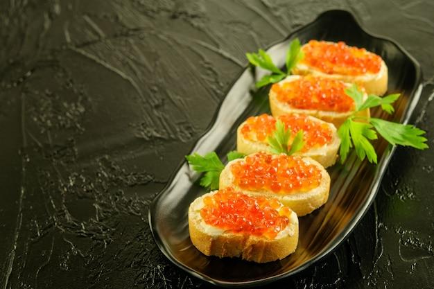 Fette di pane bianco fresco con burro e caviar_ rosso con prezzemolo sul piatto nero e su sfondo nero.