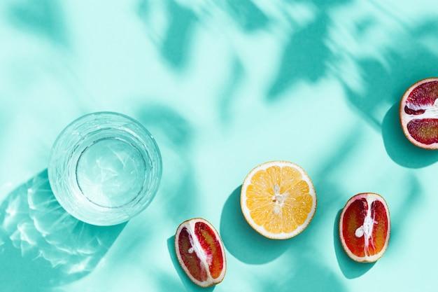 Fette di pompelmo arancia rossa limone e bere un bicchiere su sfondo turchese