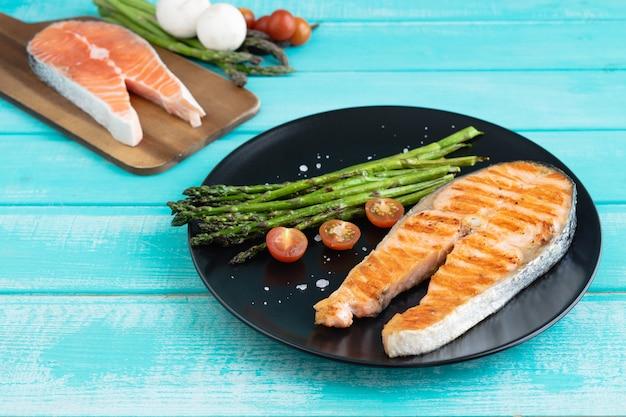 Fette di salmone alla griglia con asparagi verdi su una banda nera su uno sfondo di legno blu. copia spazio.