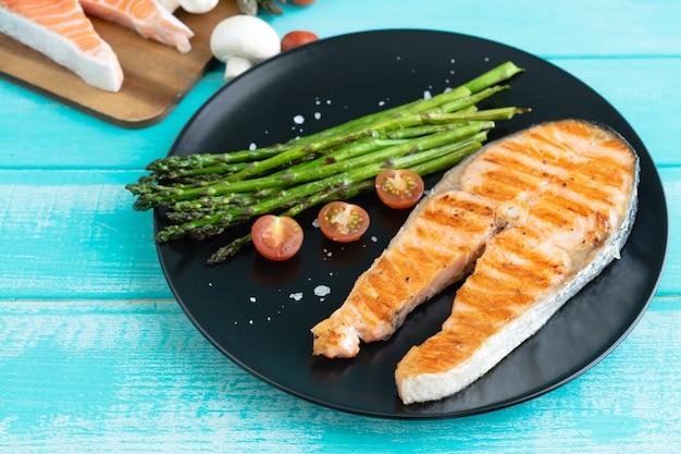 Fette di salmone alla griglia con asparagi verdi su un piatto nero su una superficie di legno blu. copia spazio.