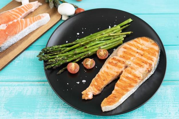 Fette di salmone alla griglia con asparagi verdi. copia spazio.