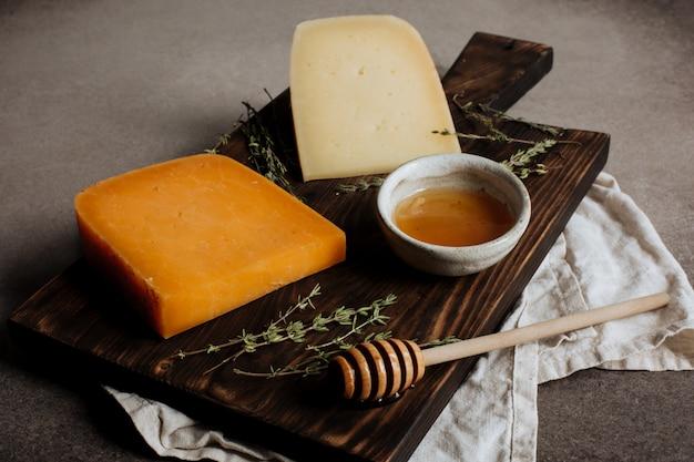Fette di formaggio a pasta dura e miele su uno sfondo grigio