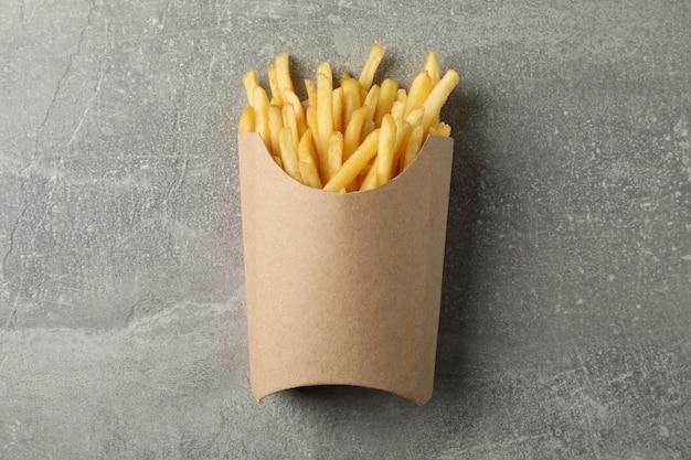 Fette di patate fritte calde in scatola su gray. vista dall'alto