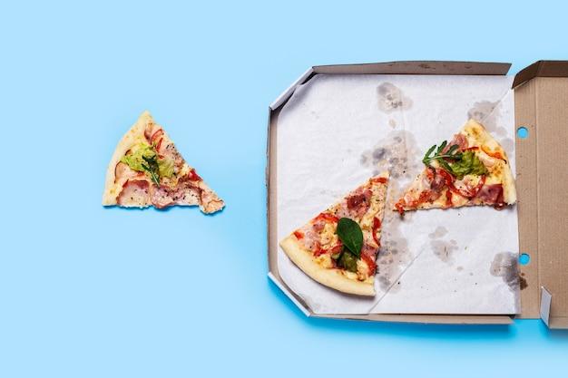 Fette di pizza fresca calda in imballaggi di cartone su un blu